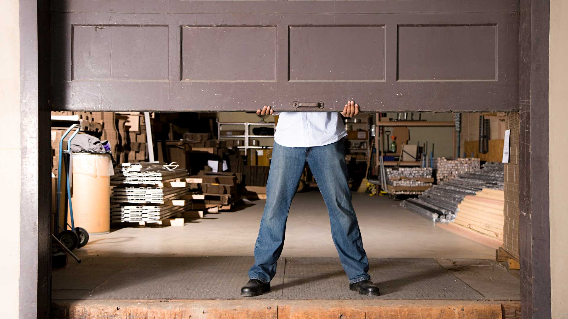 man holding garage door up بوابات الجراجات